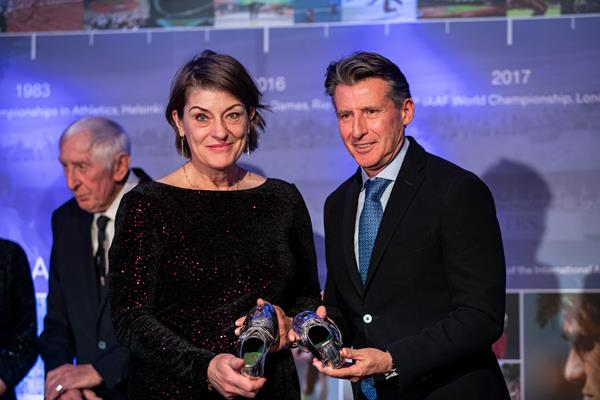 Lindsey Armstrong hands over her mother's, Diane Leather Charles, silver dipped running spikes to Seb Coe - Heritage Mile Night (© Philippe Fitte for World Athletics)