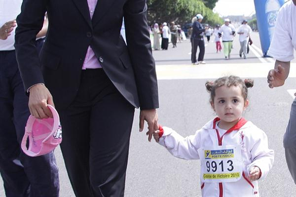 Nezha Bidouane with one of the younger runners at the Course de la Victoire in Rabat (Mohammed Benchrif)