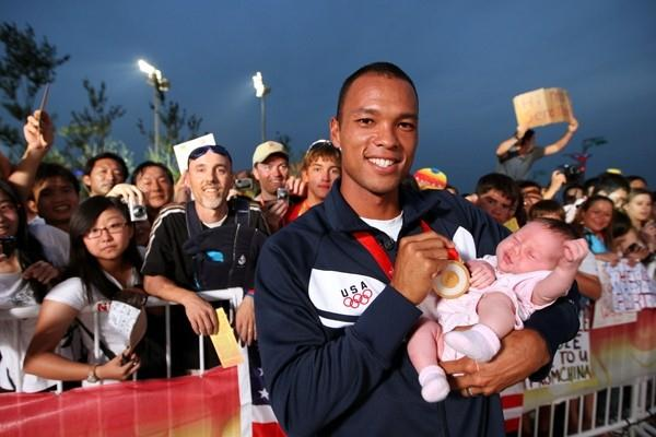 Bryan Clay celebrates his Olympic gold medal with his newlyborn (Getty Images)