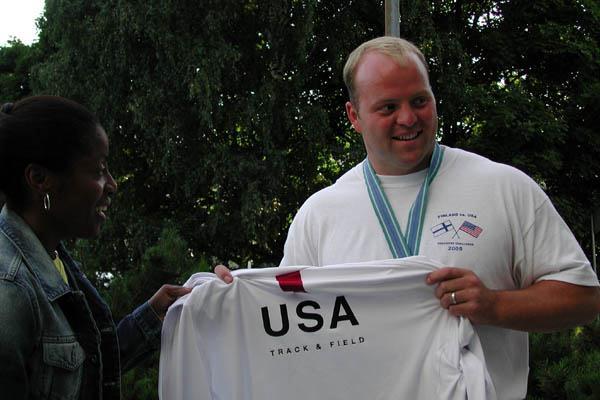 Adam Nelson of the US hands his World Championships vest to IAAF Ambassador Debbie Ferguson (Getty Images)