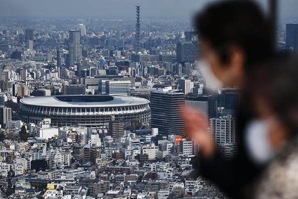 People look out at Tokyo's Olympic Stadium (AFP / Getty Images)