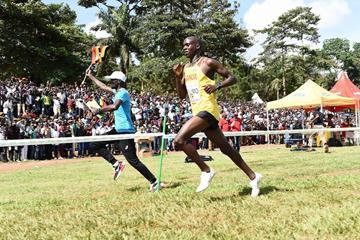 A Ugandan fan runs alongside Jacob Kiplimo during the U20 men's race at the IAAF World Cross Country Championships Kampala 2017 (Jiro Mochizuki)