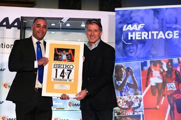 Jason Gardener presents IAAF President Sebastian Coe with Haile Gebrselassie's bib from the 1999 World Indoor Championships (Getty Images)