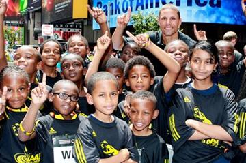 Dan O'Brien with young fans in New York City's Times Square during a '100 Kids - 100 metres - 100 years' relay event to mark the Centenary year of the IAAF, at which his inclusion into the IAAF Hall of Fame was announced.  (Victah Sailer)