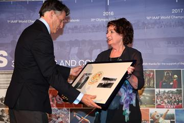 Sebastian Coe receives the framed 1908 emblem of Olympic 5 Miles champion Emil Voigt from his granddaughter Robin (Giancarlo Colombo for the IAAF)