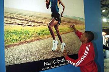 Haile Gebrselassie signing a photograph of himself on the adidas stand at the Flora London Marathon exhibition (Getty Images)