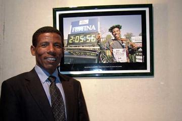 Haile Gebrselassie stands next to the picture of his Berlin Marathon victory displayed at the exhibition (Nahom Tesfaye)