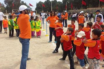 Hicham El Guerrouj shows the Tafoughalte children how to stretch (IAAF / Nestlé Healthy Kids' Athletics )