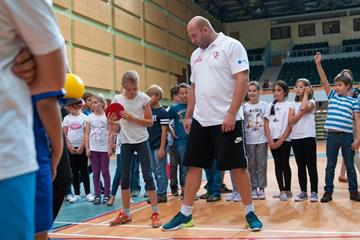 Piotr Malachowski teaching children the basics of the discus (Organisers)