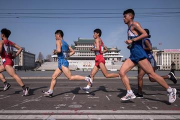 Competitors run through Kim Il-Sung square during the Pyongyang Marathon (AFP)
