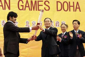 H E Sheikh Joaan Bin Hamad Al-Thani (L) official 15th Asian Games Doha 2006 Torch Relay Ambassador hands the flame to the Mayor of Beijing, Wang Qishan (Getty Images)