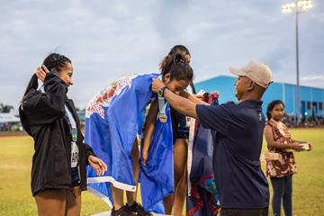 Robin Sapong Eugenio at the 2018 Micronesian Games, presenting the 200m gold medal to his daughter Zarinae Sapong  (Oceania Athletics Association)