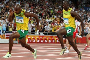 Usain Bolt hands to anchor leg runner Asafa Powell en route to running a world record of 37.10 in the 4x100m (Getty Images)