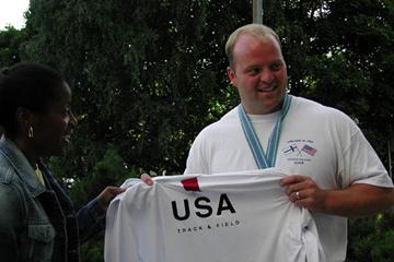 Adam Nelson of the US hands his World Championships vest to IAAF Ambassador Debbie Ferguson (Getty Images)