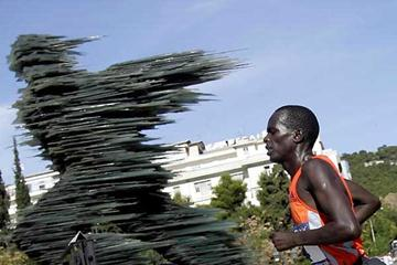 """Kenyan Henry Tarus runs to victory in front of a glass made statue called """"The runner """" during the Athens Classic Marathon race (AFP / Getty Images)"""