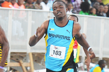 Javan Martin of The Bahamas on his way to winning the 100m at the Carifta Games (Collin Reid)