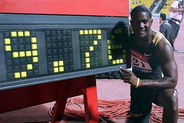 Justin Gatlin kneels next to his World record clock (AFP / Getty Images)