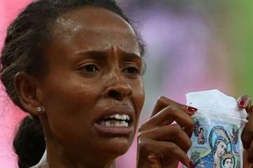 Meseret Defar of Ethiopia holds up a picture as she won the gold medal in the Women's 5000m Final on Day 14 of the London 2012 Olympic Games on 10 August 2012 (Getty Images)
