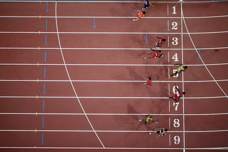 Sprinters crossing the line in the men's 100m final in Beijing ()