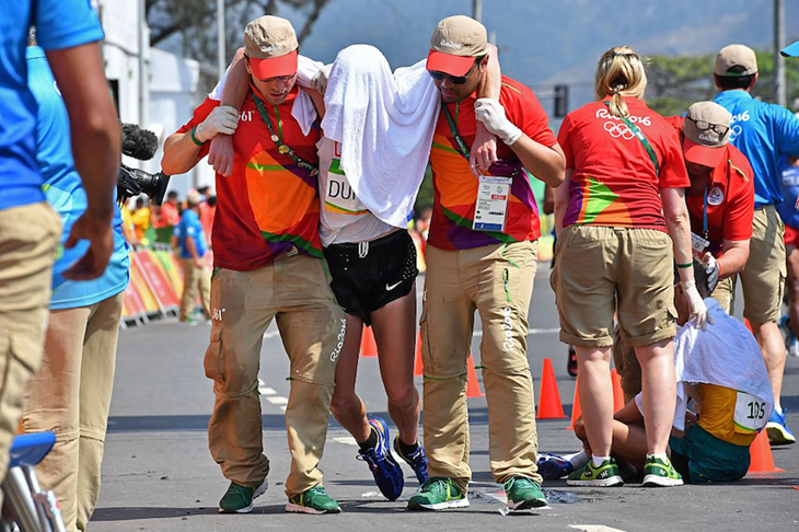 Evan Dunfee is helped off the course after finishing fourth at the Rio Olympics ()